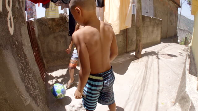 vídeos de stock, filmes e b-roll de young brazilian boys pass soccer ball down narrow alleyways through rio slums - termo esportivo