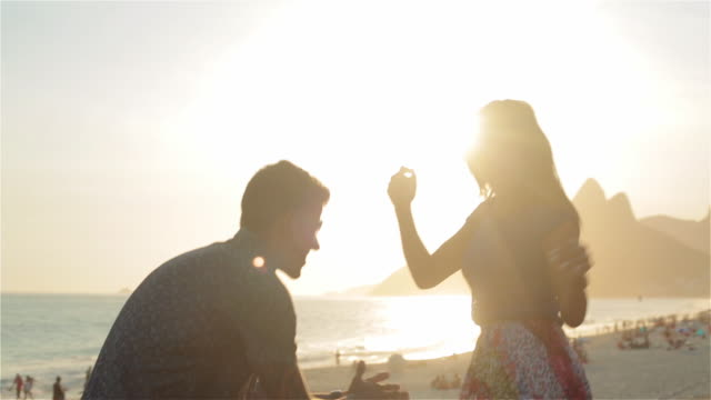 Young Brazilian couple dance in the sunlight on the beach at Ipanema