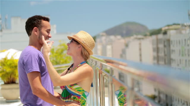Young Brazilian couple embrace on Rio hotel rooftop