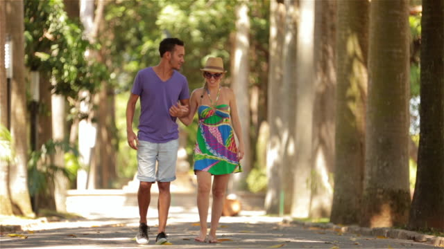 Young Brazilian couple stroll through sunny Rio park