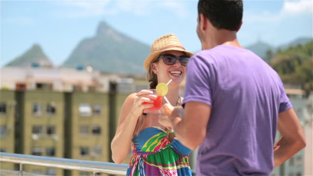 Young Brazilian couple talk and laugh on hotel rooftop