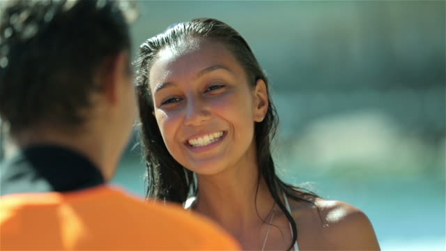 Young Brazilian girl chats and laughs with boy on sunny Copacabana Beach