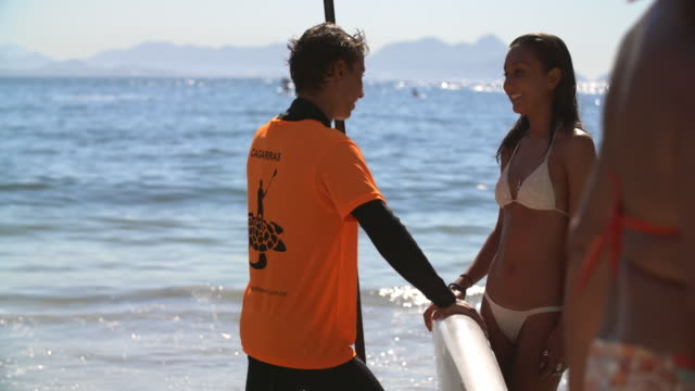 Young Brazilian girl chats with paddleboarder on sunny Copacabana Beach