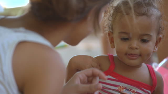 Young Brazilian girl eats sandwich and feeds baby sister in park