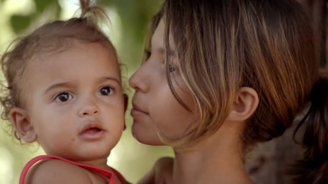 young brazilian girl kisses baby sister and smiles - geschwister stock-videos und b-roll-filmmaterial