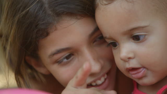 young brazilian girl points to camera and smiles with baby sister - geschwister stock-videos und b-roll-filmmaterial