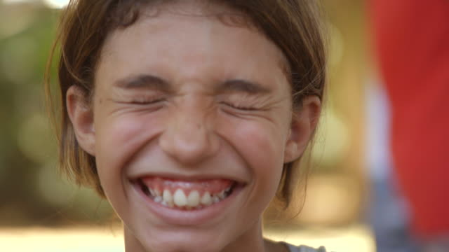 Young Brazilian girl smiles and laughs at camera