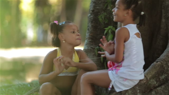 Young Brazilian girls gossip and play with ball on string in Rio public park