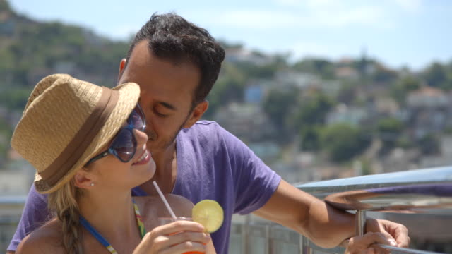 Young Brazilian man kisses girlfriend's cheek and points out over Rio skyline on hotel rooftop