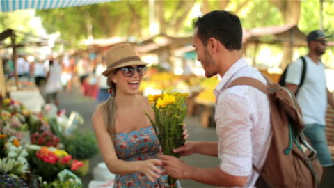 young brazilian man picks out bouquet of flowers for girlfriend in sunny marketplace - social grace stock videos & royalty-free footage