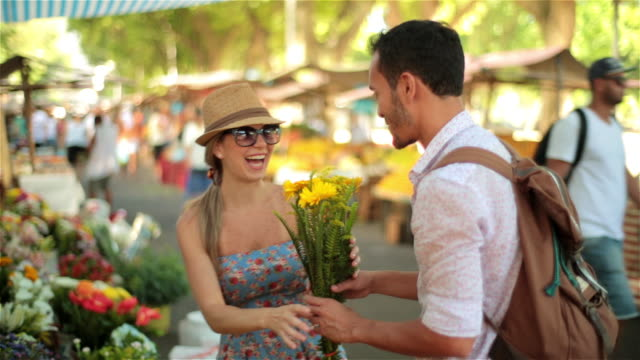 young brazilian man picks out bouquet of flowers for girlfriend in sunny marketplace - regole dell'etichetta video stock e b–roll