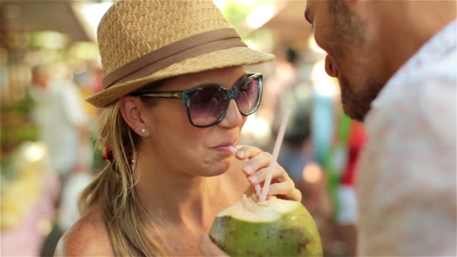 young brazilian man shares coconut drink with girlfriend and kisses her neck in public marketplace - hot passionate kissing stock videos & royalty-free footage