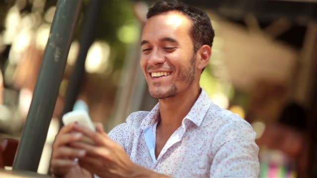 Young Brazilian man smiles and answers smartphone at outdoor caf_