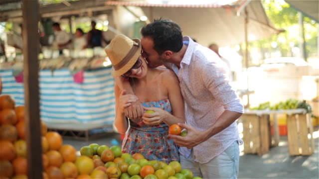 Young Brazilian man steals a kiss and wraps his arm around girlfriend as they shop for oranges at outdoor market
