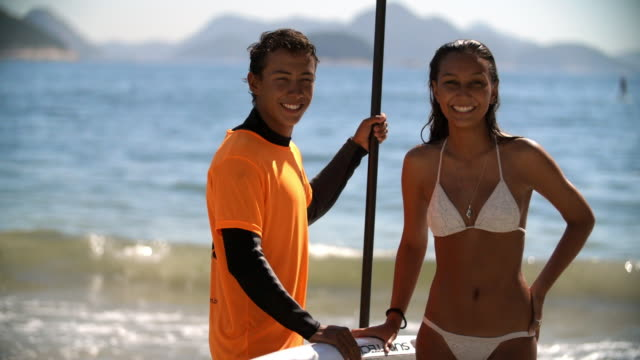 Young Brazilian paddleboarder and girlfriend smile for camera on Copacabana Beach
