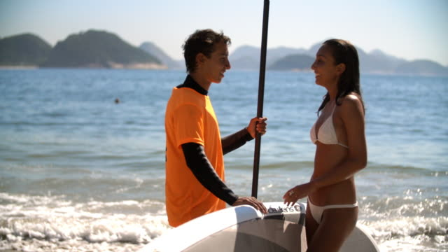 young brazilian paddleboarder chats with girl on sunny copacabana beach - teenagerpaar stock-videos und b-roll-filmmaterial