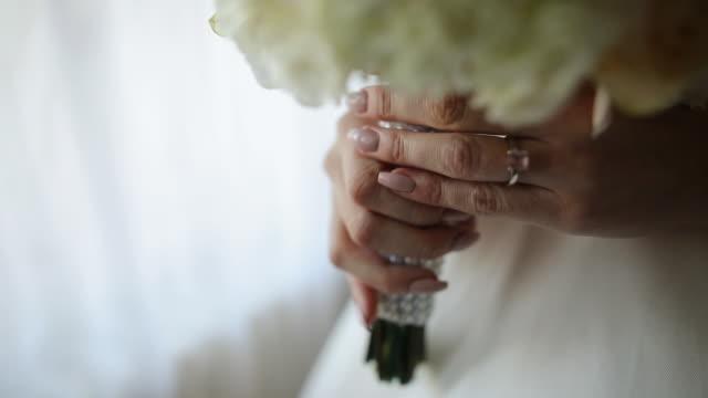 窓の近くのホテルの部屋に立っている間、結婚式のブーケを持つ指にダイヤモンドの指輪を持つ若い花嫁 - 準備点の映像素材/bロール