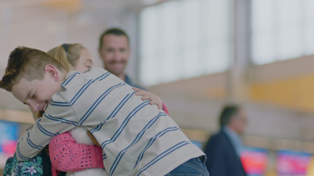 stockvideo's en b-roll-footage met slo mo. young brother and sister hug good-bye in airport terminal as smiling father looks on. - broer