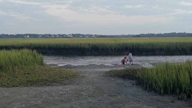 young brother and sister play in tide pools nestled in coastal marsh at dawn. - badbyxor bildbanksvideor och videomaterial från bakom kulisserna