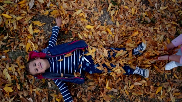 Young brother and sister playing in fallen leaves