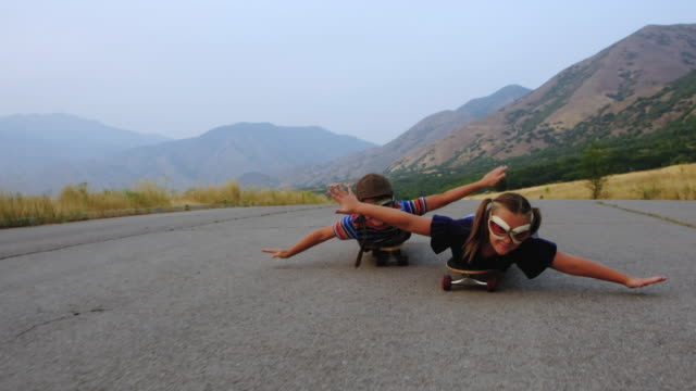 young brother and sister racing on skateboards - flying goggles stock videos and b-roll footage