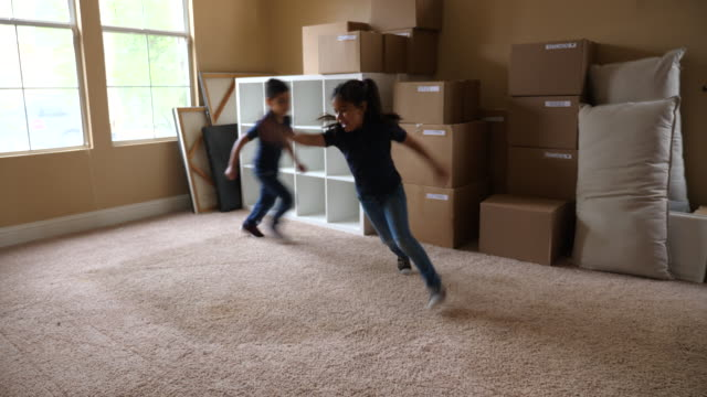 ms young brother and sister running in living room filled with boxes on moving day - sister stock videos & royalty-free footage