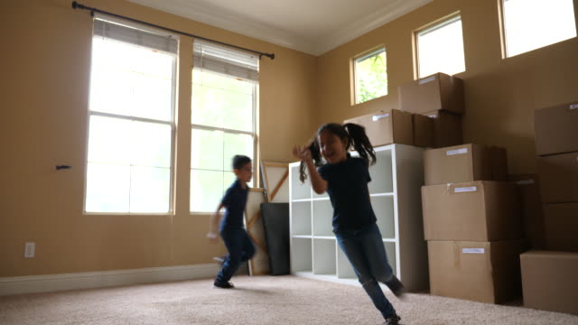 ms young brother and sister running in living room filled with boxes on moving day - rennen körperliche aktivität stock-videos und b-roll-filmmaterial