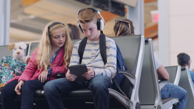 young brother and sister watch tablet while sitting in waiting area at airport terminal gate. - familie mit zwei kindern stock-videos und b-roll-filmmaterial