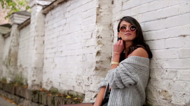 young brunette and fashion girl posing with sunglasses - jumper stock videos & royalty-free footage