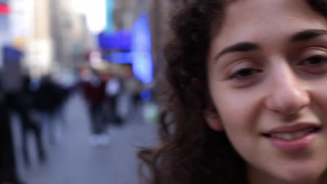 a young brunette woman smiles on a city sidewalk. - human face stock videos and b-roll footage