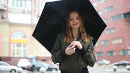 Young brunette woman stands with umbrella in her hand on the street on rainy day