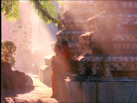 young buddhist monks in yellow robes walking + praying thru god rays on temple grounds / thailand - solo bambini maschi video stock e b–roll