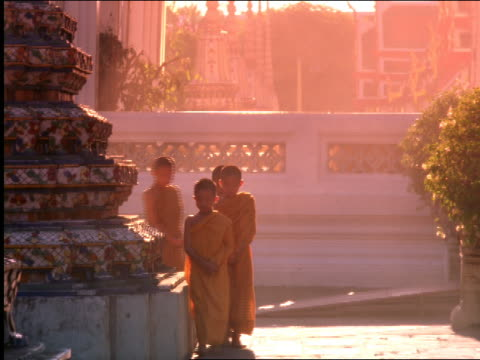 stockvideo's en b-roll-footage met young buddhist monks in yellow robes walking + praying towards camera on temple grounds / thailand - gelovige