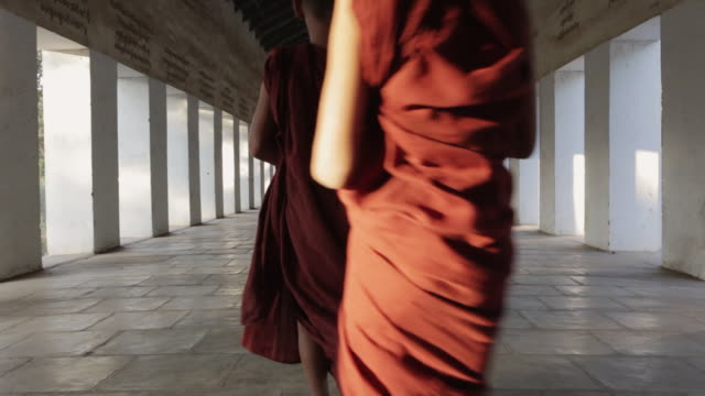 MS Young Buddhist monks walk through a temple corridor in procession while one monk runs to catch up / Bagan, Myanmar