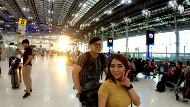 young bueatiful woman sitting on luggage  trolley and selfie with her boyfriend in airport terminal - luggage trolley stock videos & royalty-free footage