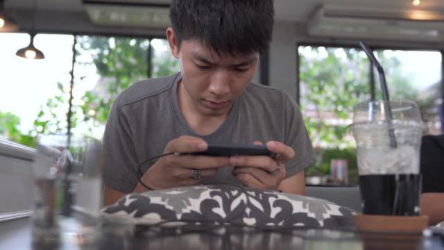 stockvideo's en b-roll-footage met young business aziatische mannen met behulp van slimme telefoon spelen mobiele spel en ontspannen met online winkelen in zijn roeping - chinese etniciteit