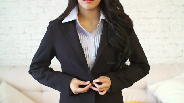 vídeos de stock e filmes b-roll de young business asian woman buttoning her suit.preparing for working in the morning. - vestuário de trabalho