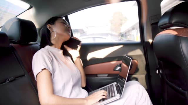 young business asian woman working on computer and mobile phone in the car. - back seat stock videos & royalty-free footage
