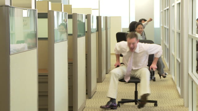 Young business colleagues racing with chairs in office