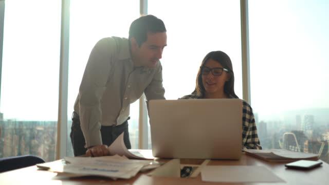 junges geschäftspaar überprüft etwas auf dem laptop und verwendet dokumente in einem coworking space - coworking stock-videos und b-roll-filmmaterial