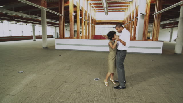 WS DS Young business couple dancing in empty office, Squamish, British Columbia, Canada