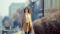 Young business lady walking down the street in early spring. She is happy and enjoys life. Sunny day.