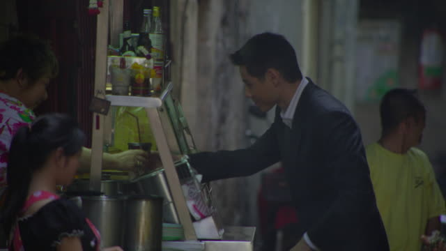 ms cu young business man buying drink at street food stall, bangkok, ayuthaya, thailand - see other clips from this shoot 1448 stock videos and b-roll footage
