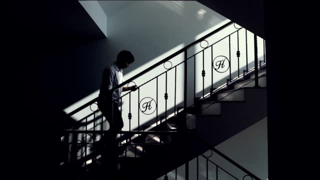 Young business man climbing stairs and using mobile phone in office.
