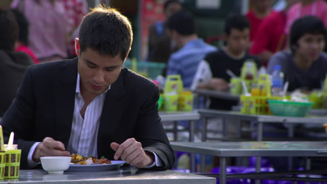 ms selective focus young business man eating at outdoor restaurant, bangkok, ayuthaya, thailand - see other clips from this shoot 1448 stock videos and b-roll footage