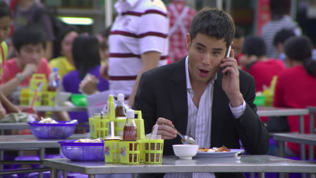 ms selective focus young business man eating while talking on mobile phone at outdoor restaurant, bangkok, ayuthaya, thailand - see other clips from this shoot 1448 stock videos and b-roll footage