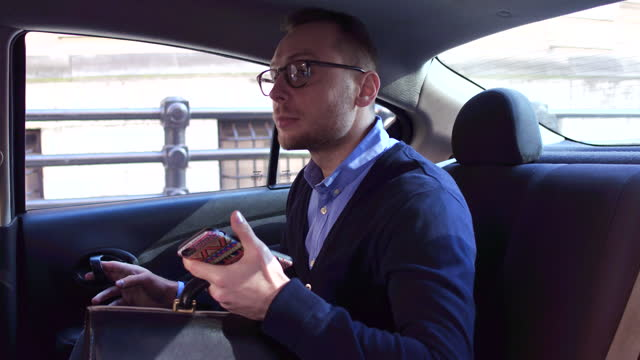 young business man gets out of back seat of car, daytime - aussteigen stock-videos und b-roll-filmmaterial
