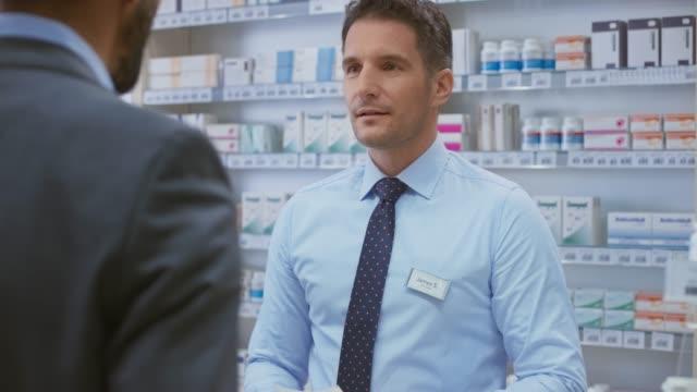 vídeos de stock e filmes b-roll de young business man handing the male pharmacist his prescription - empregado de balcão