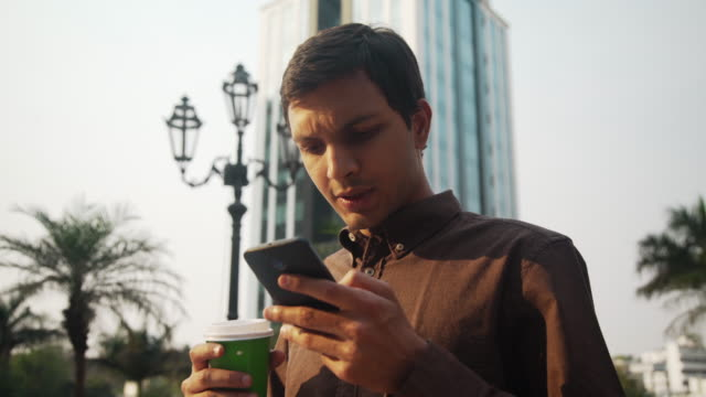 Young business man in India using cellphone