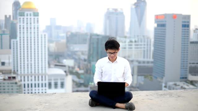 vídeos de stock, filmes e b-roll de jovem homem de negócios usando o computador portátil e olhar para a cidade, culinária asiática - viagem de negócios